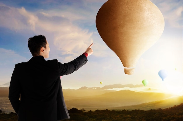 夕焼け空の背景で飛んでいるカラフルな気球を指すアジアのビジネスマンの背面図