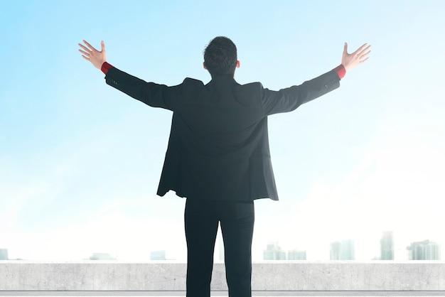 高層ビルの背景と屋上に上げられた手で立っているアジアのビジネスマンの背面図