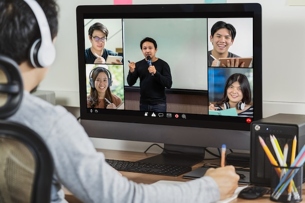 동료와 화상 회의를 통해 일하는 아시아 사업가의 뒷모습과 온라인 회의