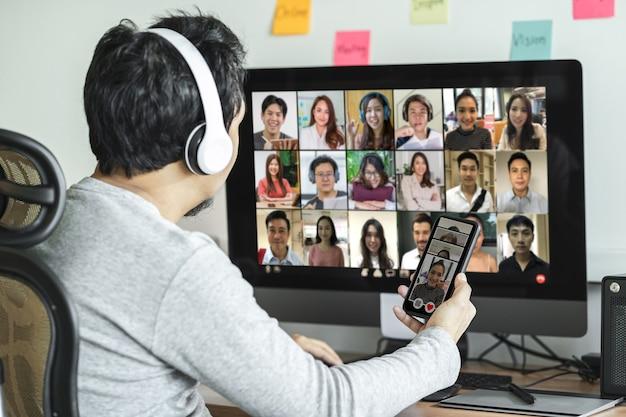 Вид сзади азиатского мужчины, использующего настольный компьютер и мобильный телефон для выбора женщины
