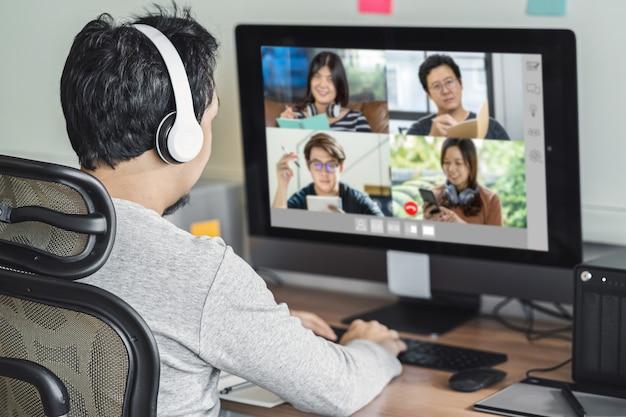동료와 화상 회의를 통해 일하는 아시아 남성의 뒷모습과 온라인 회의