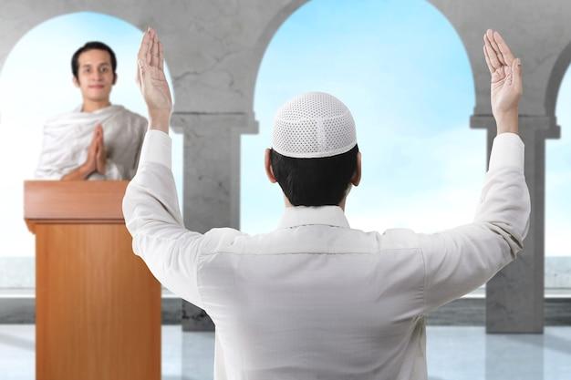 Вид сзади азиатского мусульманина, стоящего с поднятыми руками и молящегося в мечети