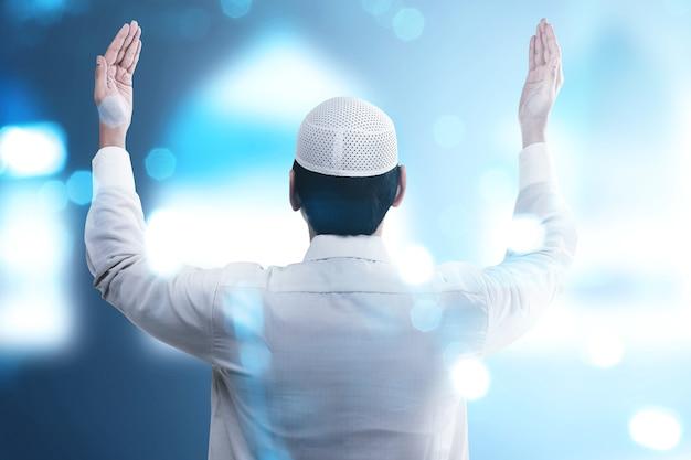手を上げて立って、ぼやけた明るい背景で祈るアジアのイスラム教徒の男性の背面図