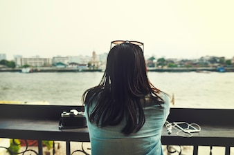 Rear view of asian tourist woman sitting by the riverside