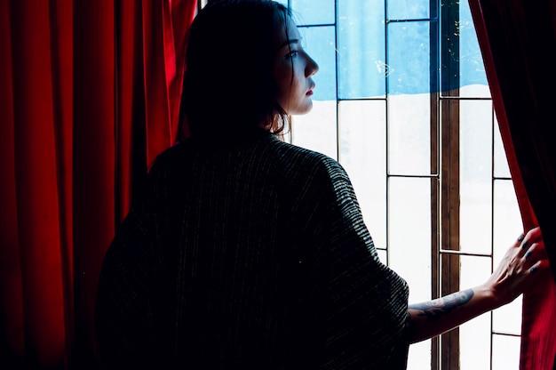 창이에 서 아시아 여자의 뒷 모습