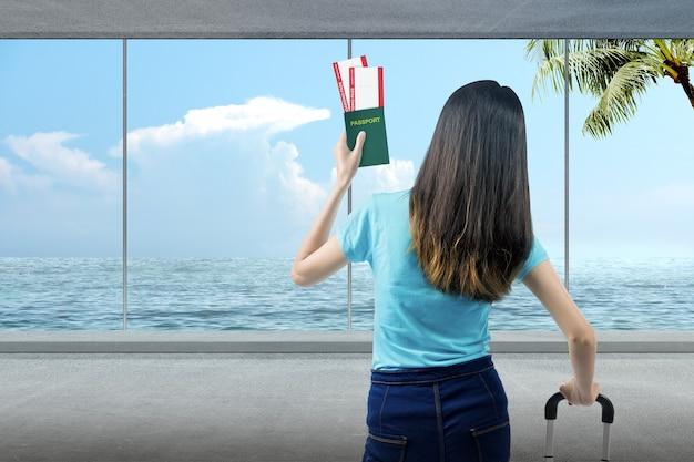 바다가 보이는 리조트에서 티켓과 여권을 들고 여행가방을 들고 있는 아시아 여성의 뒷모습