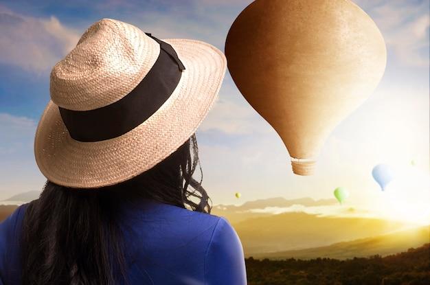 夕焼け空の背景で飛んでいるカラフルな気球を見ている帽子とアジアの女性の背面図