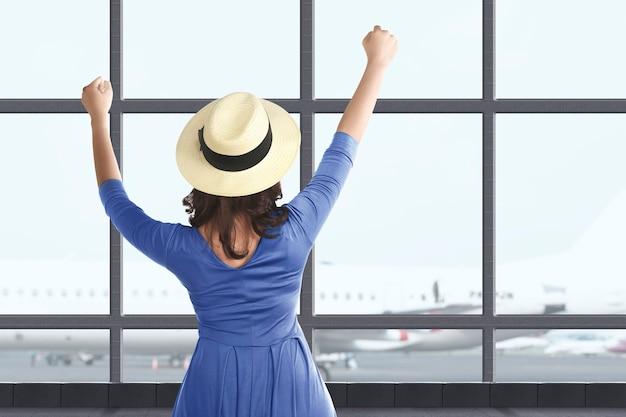 공항 터미널에서 여행하는 모자와 함께 아시아 여자의 후면 볼 수 있습니다. 새로운 노멀 여행