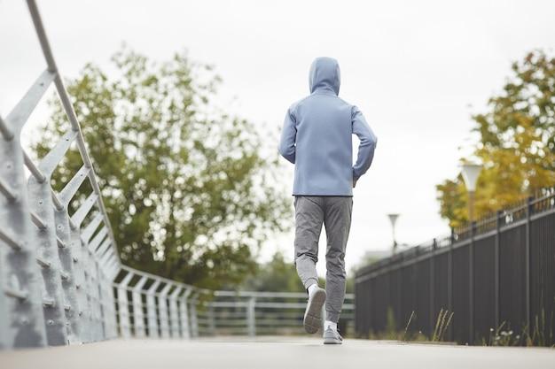公園でジョギングしているスポーツウェアのアスリートの背面図