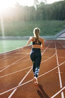 열심히 준비하는 아침 가벼운 훈련에 트랙에서 빠르게 달리는 운동 선수 여성의 후면보기