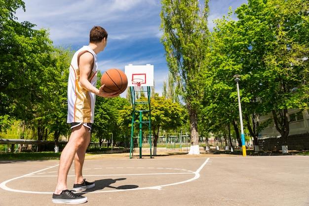 무성 한 녹색 코트의 야외 코트에서 키의 상단에서 운동 젊은 남자 무료 던지기 농구의 후면보기