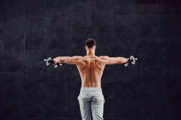 暗い壁の前に立っている間ダンベルを保持している魅力的な筋肉白人金髪上半身裸の男の後姿