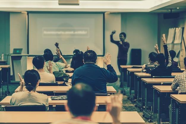 회의실에서 질문에 답하기 위해 손을 위로 들고 응답하는 청중의 후면 보기