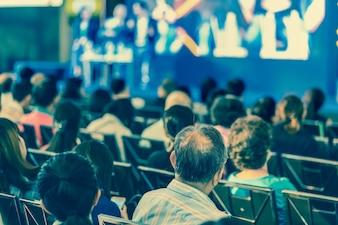 会議室またはセミナーのステージで聴衆の話を聞いている人のリアビュー