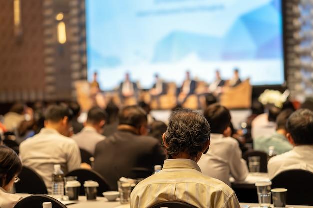 Вид сзади аудитории слушают докладчиков на сцене в конференц-зале или семинаре меня