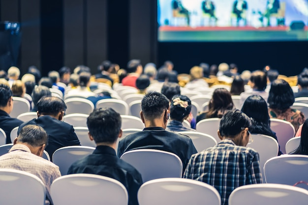 会議ホールやセミナー会議、ビジネス、投資の概念についての教育のステージで聴衆のスピーカーを聞いての背面図