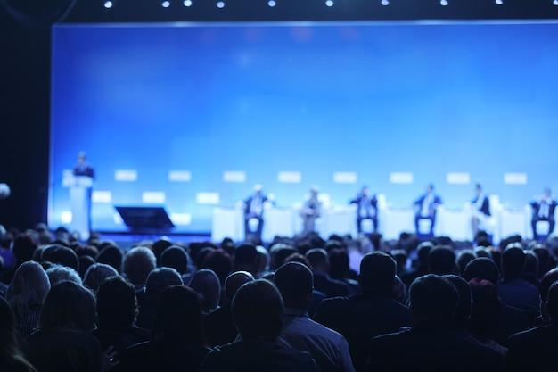 会議ホールまたはセミナー会議、ビジネスおよび教育の概念のステージ上のスピーカー上の聴衆の背面図