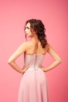 Вид сзади элегантной женщины в нежном элегантном розовом платье с открытой спиной, изолированной на розовом ба ...