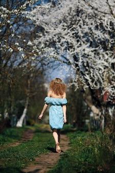 숲에서 걷는 맨발 여자의 뒷 모습