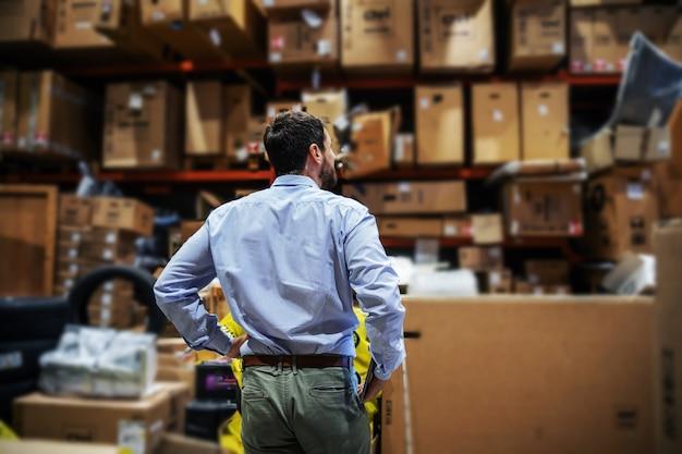 Вид сзади бородатого бизнесмена, стоящего на складе экспортной фирмы и проверяющего коробки, готовые к отправке.