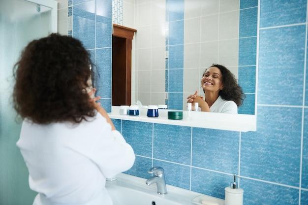 흰색 와플 가운을 입은 아름다운 아프리카계 미국인 여성의 뒷모습이 거울에 반사되어 귀엽게 웃고 있습니다.