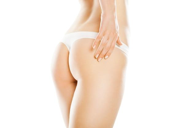 白い背景で隔離の長い脚を持つ美しい白人女性の背面図