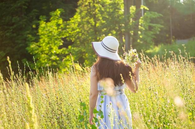 晴れた夏の日に野生の花の間を歩く美しい若い女性の背面図。夏の自然とのコミュニケーションの喜びの概念