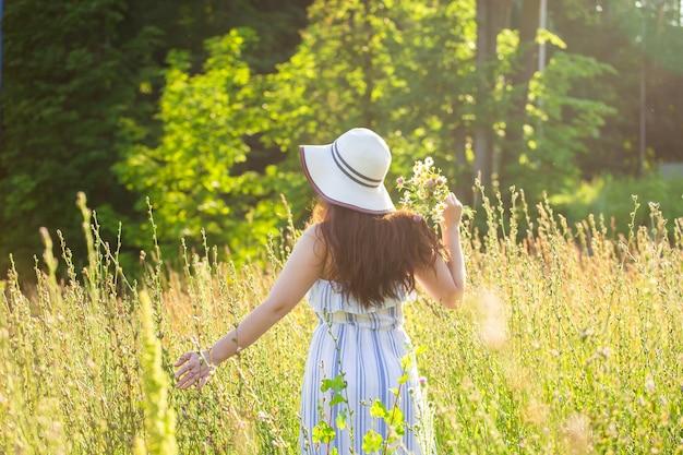 晴れた夏の日に野生の花の間を歩く美しい若い女性の背面図。喜びの概念