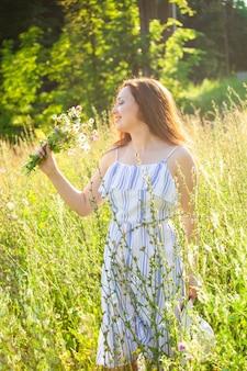 晴れた夏の日に野生の花の間を歩く美しい若い女性の背面図。夏の自然とのコミュニケーションの喜び
