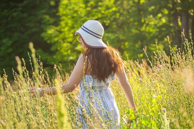 晴れた夏の日に野生の花の間を歩く美しい若い女性の背面図