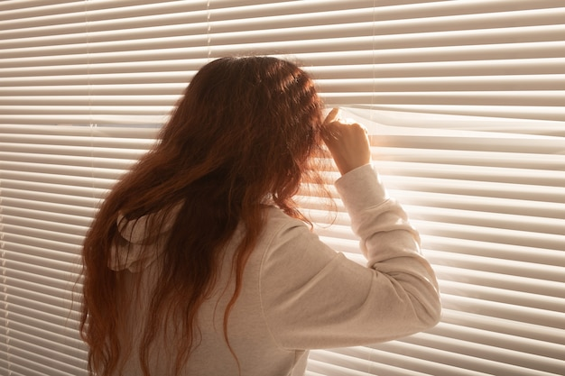 Вид сзади красивой молодой женщины с длинными волосами заглядывает через отверстие в жалюзи и смотрит