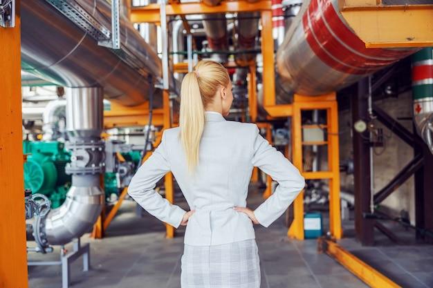腰に手を置いて暖房設備に立っているフォーマルな服装の金髪の女性の上司の背面図。