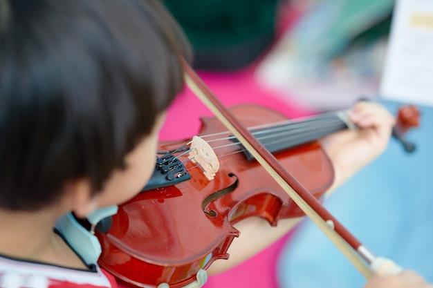少年の後姿がメモ背景をぼかし、セレクティブフォーカスでバイオリンを弾く