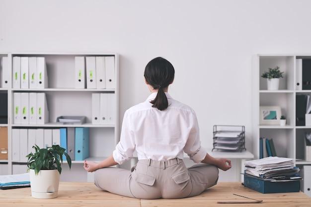 テーブルの上の蓮華座に座って黙想しているブルネットのオフィスの女性の背面図