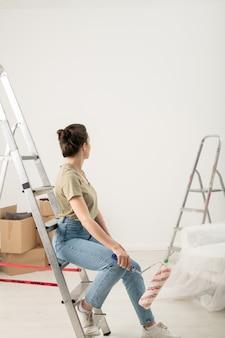 はしごのステップにペイントローラーと座って、塗られた壁を見ているジーンズのブルネットの女性の背面図