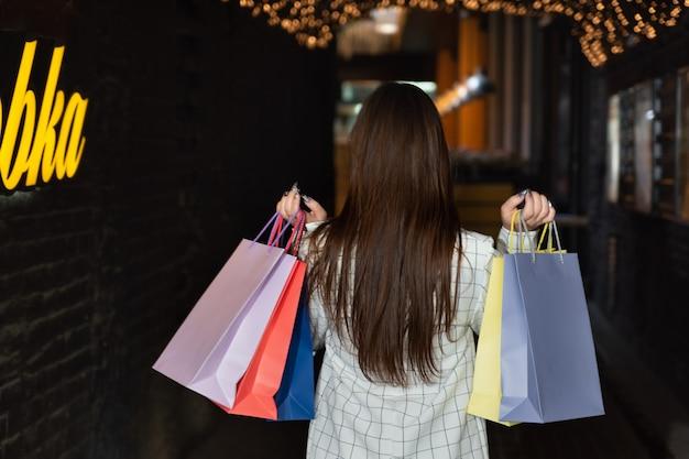 그녀의 손에 다채로운 종이 쇼핑백과 갈색 머리 여자의 후면 보기. 성공적인 쇼핑.