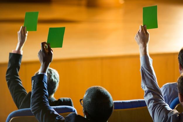 Вид сзади руководителей предприятий показывают свое одобрение, подняв руки в конференц-центре