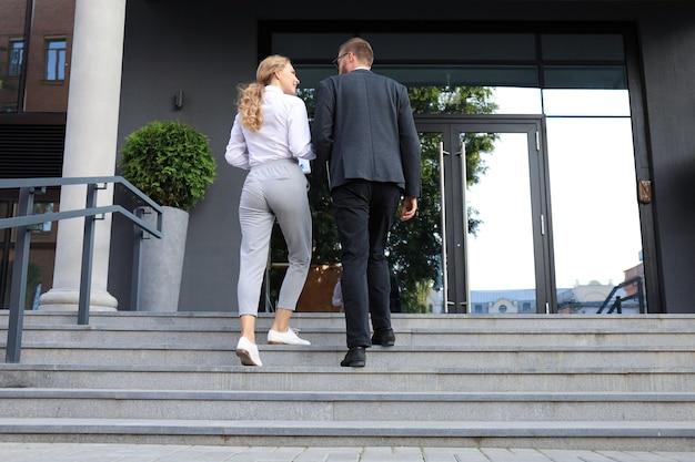 オフィスセンターを歩いているビジネスの男性と女性の背面図。