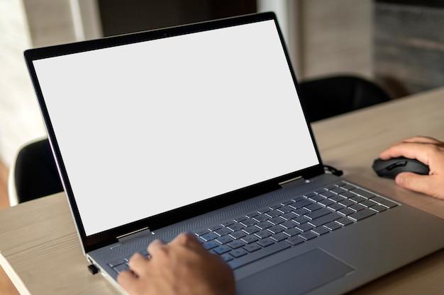 Вид сзади деловых рук человека, занятого использованием ноутбука за офисным столом, с copyspace
