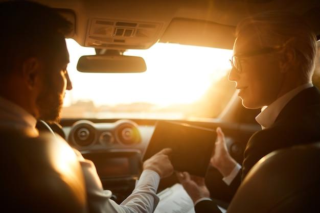 디지털 태블릿을 사용하고 차에 앉아 온라인 프로젝트를 논의하는 사업 사람들의 후면보기
