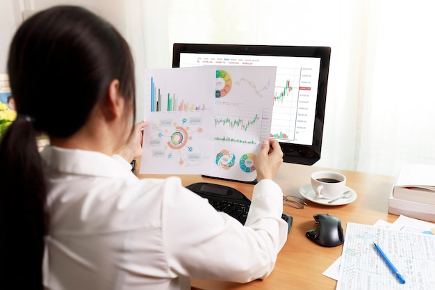 Вид сзади деловой женщины, работающей в офисе с компьютером, держа бумагу для отчета диаграммы и смотреть. деловые люди, работающие дома с бумагой и экраном пк. бизнес и финансы, концепция работы на дому