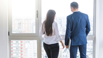 Rear view of businessman and businesswoman looking out of window