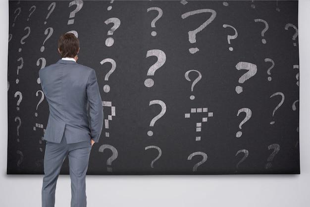 Вид сзади бизнесмен, глядя на знаки вопроса