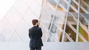 Rear view of businessman standing in front of modern corporate building