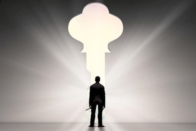 열쇠 구멍으로 서 있는 사업가의 뒷모습