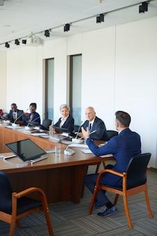 Вид сзади бизнесмена, разговаривающего со своими коллегами, сидя за столом в зале заседаний