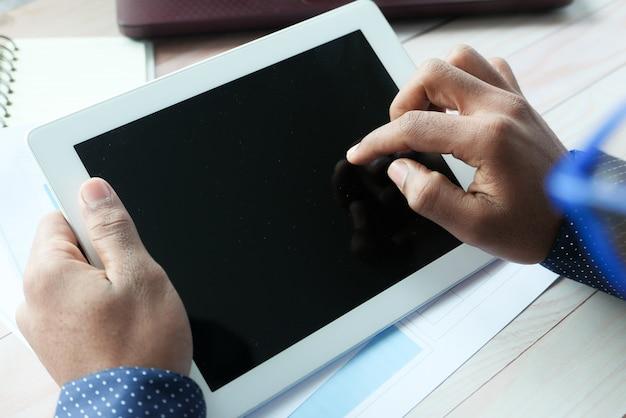 사무실 책상에 디지털 태블릿을 사용하는 사업가의 후면 볼 수 있습니다.