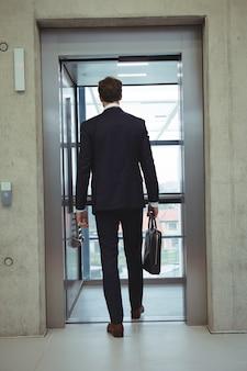 エレベーターに歩くビジネスマンの背面図