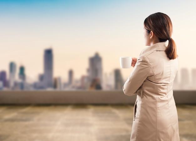 都市の景観を背景に立っている実業家の背面図