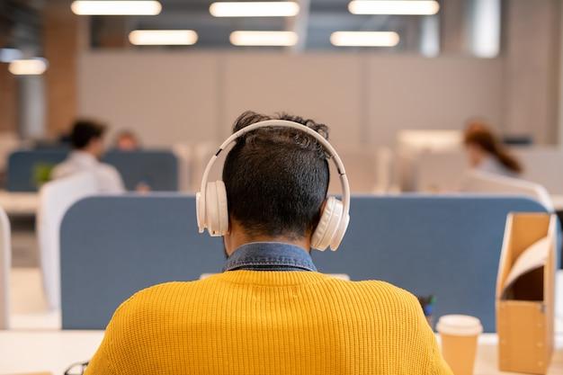 オープンスペースのオフィスのテーブルに座って、オーディオファイルを聞いて明るいセーターを着ているワイヤレスヘッドフォンで忙しいブルネットの男の後姿